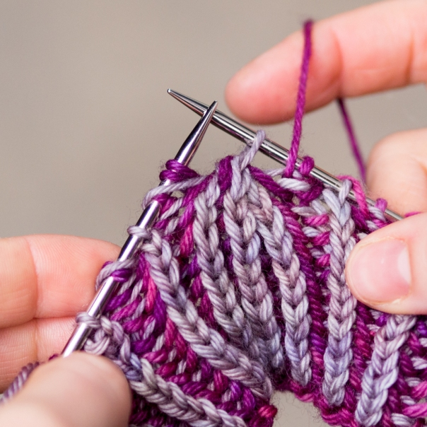 Yarn over and slip the decreased MC stitch from the previous round. Don't forget to bring the yarn to the front between the needles before beginning the decrease.